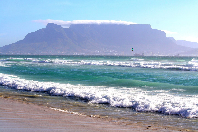 De tafelberg gezien vanaf een strand met golven - Kaapstad, Zuid Afrika